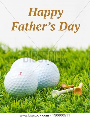 Three white golf balls and tees with a Fathers Day inscription.