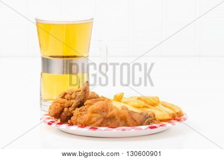 Small paper plate with pieces of southern fried chicken and french fried potatoes.