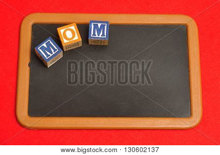 Mom spelled with colorful alphabet blocks and a red heart on a blackboard