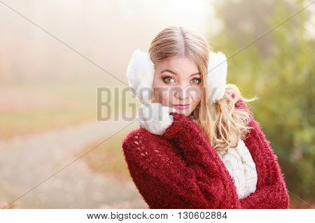 Portrait of pretty attractive fashionable woman in fall forest park. Gorgeous young girl in white fur earmuffs and maroon sweater pullover. Autumn winter fashion.