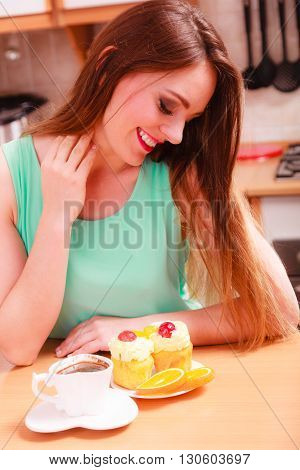 Woman with cup of coffee and delicious gourmet sweet cream cake cupcake and orange. Lovely girl sitting in kitchen with hot beverage having breakfast. Appetite and gluttony concept.