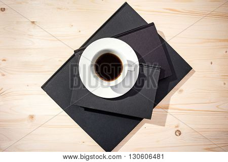 Top view of coffee cup on closed notepads