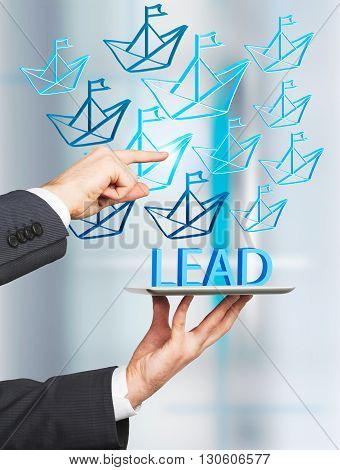 Lead generation concept with businessman hands directing paper boat icons into tablet