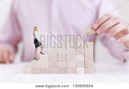 Success concept with businessman building and businesswoman walking on wooden block stairs