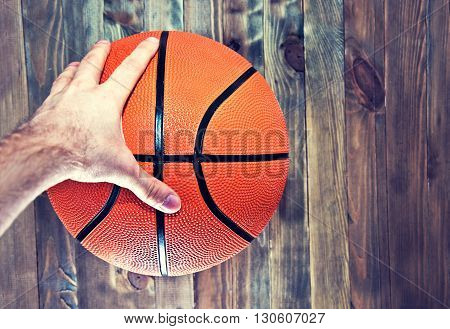 Basketball ball on wooden hardwood floor in the basketball court grabbing by hand. Retro vintage picture. Sport concept.
