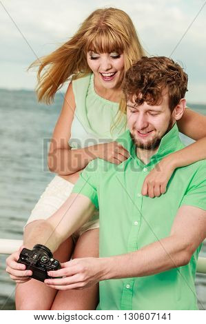 Young couple in love on sea pier with camera. Boyfriend and his his lovely girlfriend taking self portrait outdoor