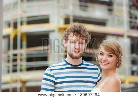 Real estate and family concept - young couple on front of new big modern house dreaming about home
