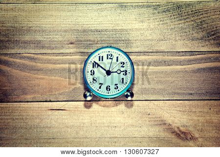 Old clock on the wooden background. Retro vintage picture. Time concept.
