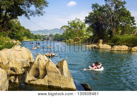 Vang Vieng, Laos - December 10, 2013: Tourists tubing down the Song River at Vang Vieng, Vientiane Province, Laos.