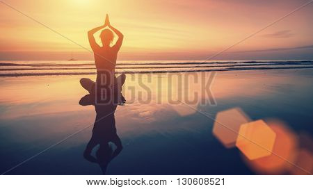 Amazing yoga background, silhouette of woman on the beach at  beautiful sunset, meditation and mindfulness.