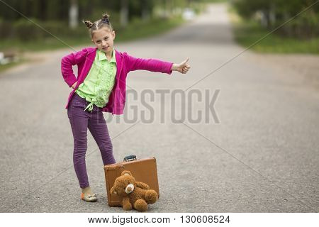 Hitch-hiking little funny girl on the road with a suitcase and a Teddy bear.