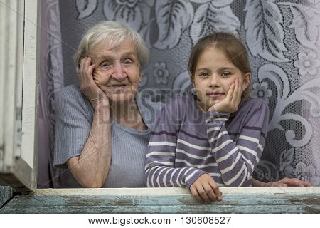 Grandmother with her granddaughter looking out the window of house.