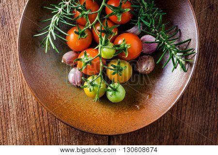 Cherry Tomatoes, Garlic And Rosemary In Ceramic Plate