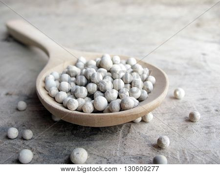 closeup white pepper seed on wooden spoon