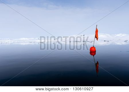 Red buoy floating in the Brepollen bay, Spitsbergen, Arctic