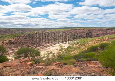 Kalbarri National Park elevated scenic views of the Murchison River Gorge with sandstone bluffs and native flora in Kalbarri, Western Australia under a blue sky with clouds.