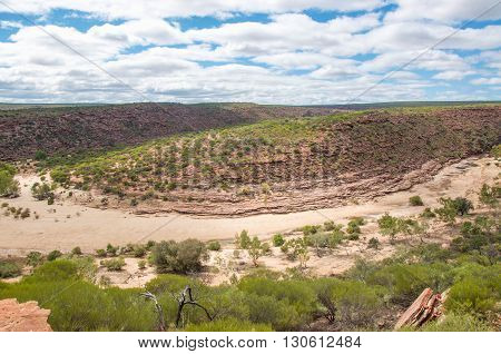 Landscape view from above of the Murchison River gorge during a drought with sandstone and native plants under a blue sky with clouds in Kalbarri, Western Australia.