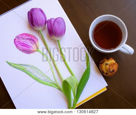 Mixed art. Composition of sketch of violet tulip and two fresh tulips forming beutiful bouquet. Tea in white cup and mini cake. Wooden brown background. Creativity consept. Relax. Be creative. Pencil drawing on artistic paper sketch book. Green leafs