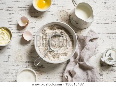 Baking rustic light background. Raw ingredients for baking - flour eggs milk sugar butter cream. Rustic style