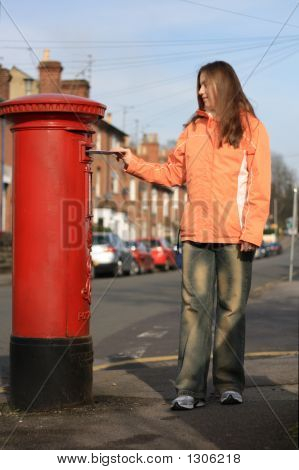 Girl Posting Letter To Red British Postbox