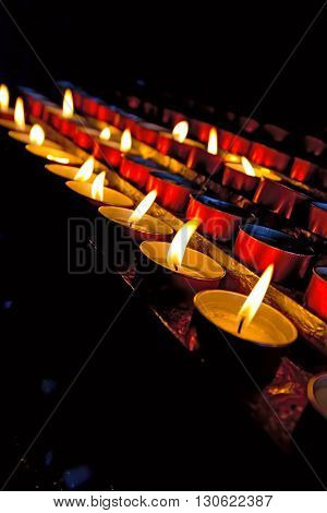 A group of blurred and red votive candles in the darkness of a church