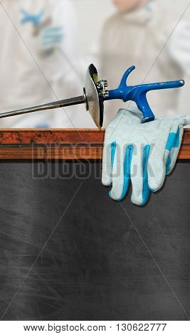 Empty chalkboard with wooden frame a detail of a fencing foil glove and blurred fencer. Template for fencing sport