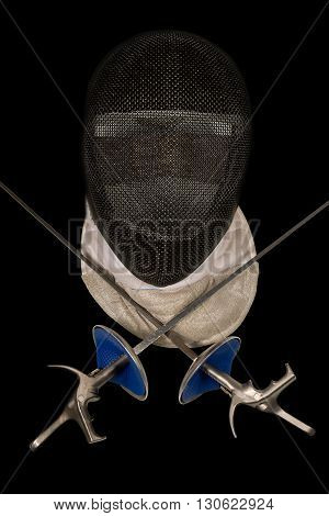 Fencing foil equipment. Two fencing foils with pistol grip and a fencing mask. Isolated on black background