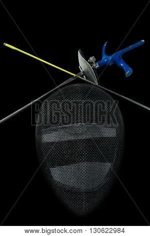 Fencing foil equipment. Two fencing foils with pistol grip and tip and a fencing mask. Isolated on black background