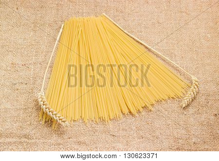 Uncooked dried long pasta and two wheat spikes on a sackcloth