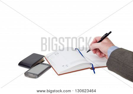 Male hand with pen over business diary with blue page-marker ribbon wallet for business cards and mobile phone on a light background