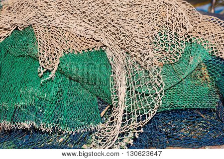 Close up of green white brown and blue fishing net