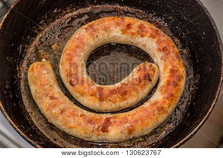 Fried homemade sausage during it cooking in a frying pan