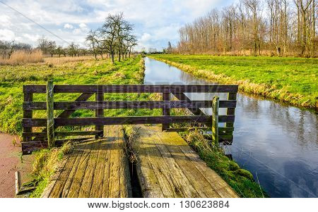 Rural landscape in the Netherlands with a simple bridge and a small stream. It's a sunny day in autumn but the clouds are coming.