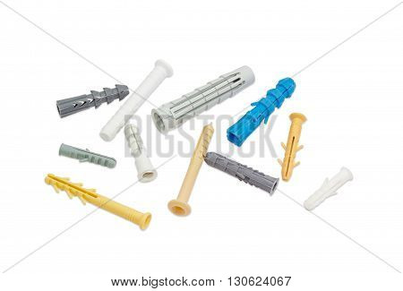 Plastic wall plugs of different sizes and colors on a light background