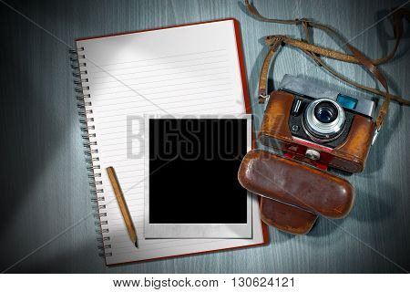 Old and vintage camera with leather case empty notebook with pencil and an instant photo frame on a wooden desk