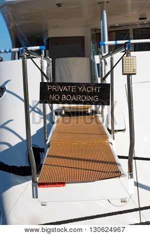 Black sign on a gangway of a luxury yacht with text Private yacht no boarding