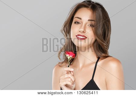 Beautiful Woman With Rose Flower On Gray Background