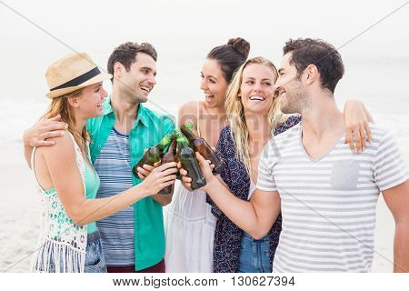Group of happy friends toasting beer bottles on the beach