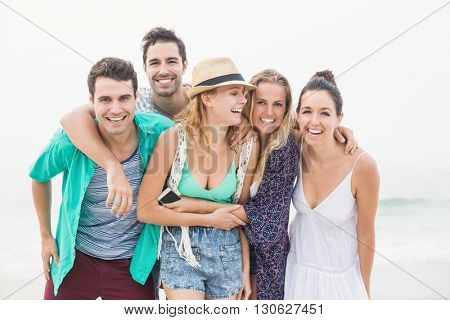 Group of friends standing together and having fun on the beach