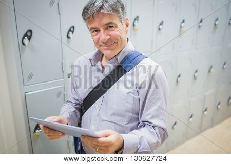 Portrait of professor using a digital tablet in locker room at university