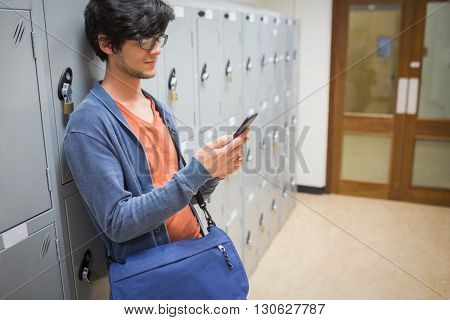Student standing in locker room and using mobile phone