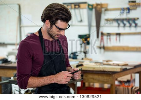 carpenter on the phone in a dusty workshop