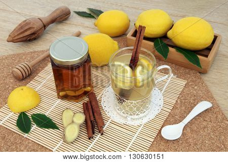Hot lemon, honey and ginger drink for cold remedy in a glass tea cup with cinnamon stick spice and fresh fruit   on bamboo over cork and oak background.