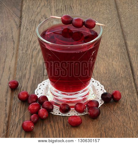 Cranberry juice health drink with fresh fruit on oak background. High in vitamins, anthocyanins, and antioxidants.