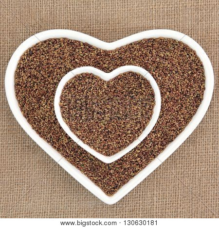 Alfalfa seed health food in heart shaped porcelain bowls over hessian background.