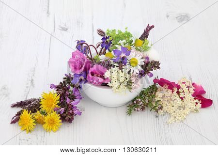 Flower and herb selection used in natural herbal medicine over distressed wooden background.