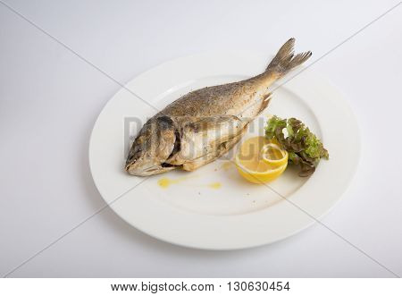 Grilled whole dorado fish with lemon and lettuce