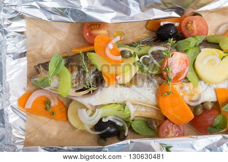 Whole baked fish with different vegetables and herbs