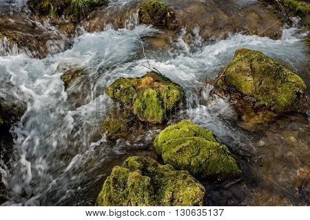 Source of the river that makes waterfalls over rocks covered with moss in early spring