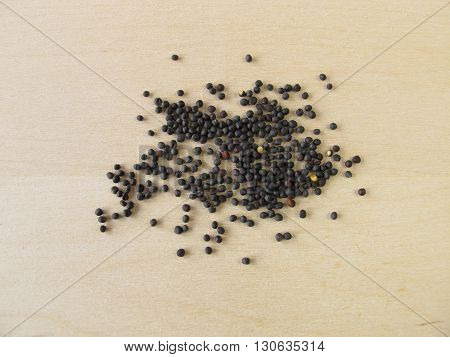 Canola seeds for oil on wooden board